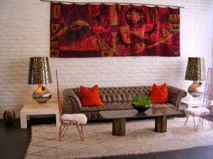 Brown leather Chesterfield sofa in a designer living room with red pops