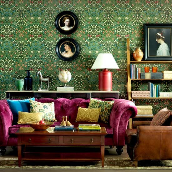 Magenta pink Chesterfield sofa in a designer living room. Fantastic emerald green wallpaper