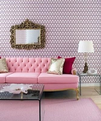 Pale pink tufted tuxedo sofa in a designer feminine living room. Fantastic use of gold with the purple and pink wallpaper