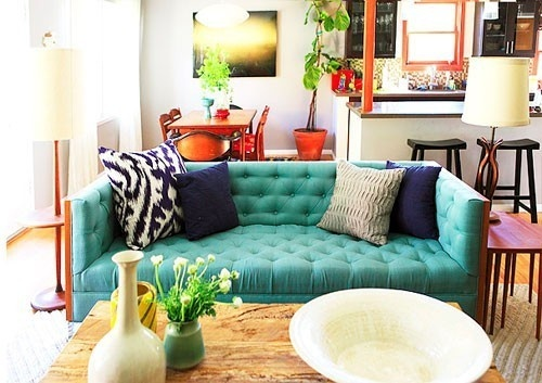 Turquoise blue tufted tuxedo sofa in a designer living room with pops of navy and natural woods and textures